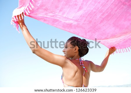 Back view of an attractive african american woman holding an bright pink sarong in the air with her arms raised against a clean blue sky background. - stock photo