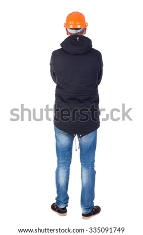 Back view of an engineer in  construction helmet stands.  Standing young guy in parka. Rear view people collection.  backside view of person.  Isolated over white background. - stock photo