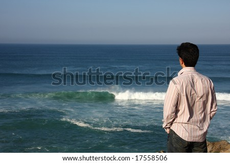 Back view of an young man looking to te sea