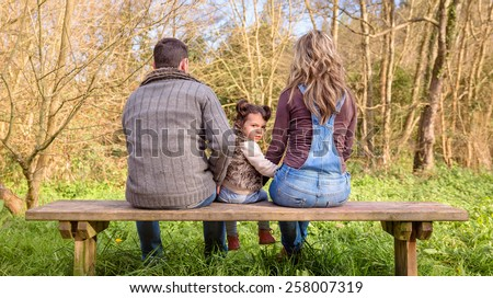Back view of angry little girl looking to the camera between of man and woman sitting on a wooden bench in the park - stock photo
