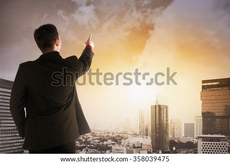Back view of asian business man looking the city from the rooftop - stock photo