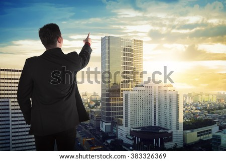 Back view of asian business man looking the sky on the building rooftop - stock photo