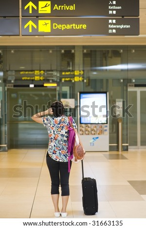 back view of asian girl getting lost at singapore's changi airport terminal - stock photo