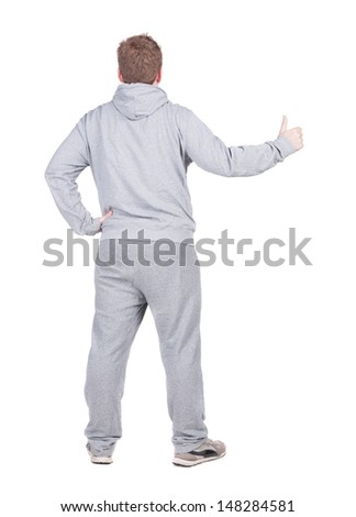 Back view of athlete man in gray tracksuit. shows thumbs up.   Rear view people collection.  backside view of person.  Isolated over white background.