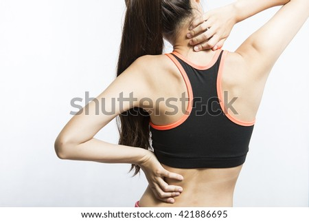 Back view of athletic young woman in sportswear touching her neck and lower back muscles by painful injury