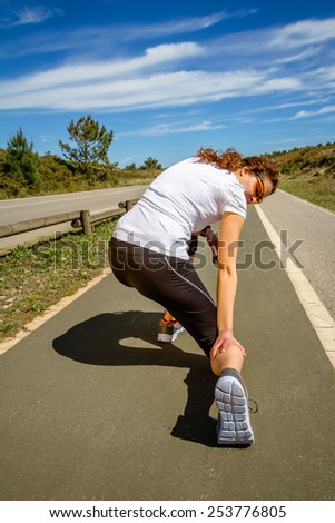 Back view of athletic young woman with sportswear suffering pain in her leg calf by a muscle cramp on a training. Sport injuries concept. - stock photo