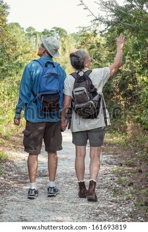 Back-view of attractive mature or senior couple holding hands while hiking on a nature trail wearing backpacks. - stock photo