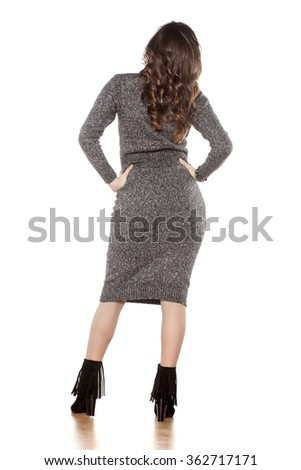 back view of attractive woman in a gray tight dress posing on white - stock photo