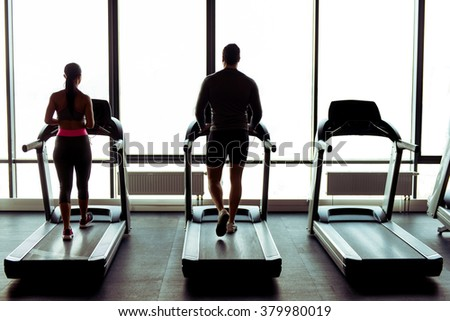 Back view of attractive young muscular man and woman running on a treadmill in gym
