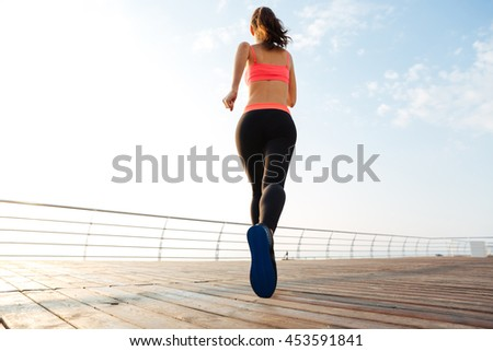 Back view of attractive young woman athlete running outdoors on wooden terrace