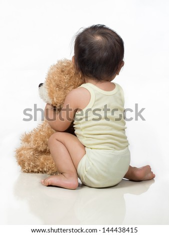back view of baby hugging stuffed bear animal toy - stock photo
