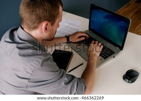 Back view of bearded businessman typing on laptop keyboard
