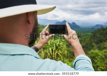 Back view of bearded man is taking photo with cell telephone camera, while is standing on mountain with subtropical forest. Young hipster guy is shooting video on smart phone of a amazing wild nature - stock photo