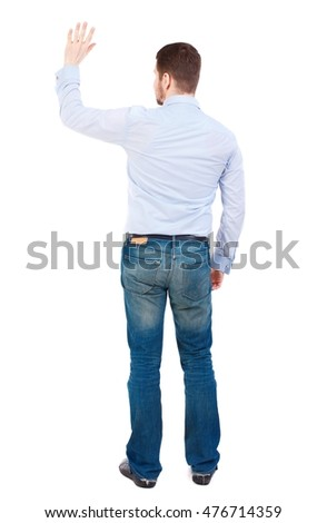 Back view of beautiful business man welcomes. businessman in white shirt cheerfully waving his hand in greeting.