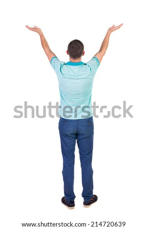 Back view of Beautiful man in jeans looking at wall and Holds  hand up.  young brunette standing. Rear view people. Isolated over white background.  - stock photo