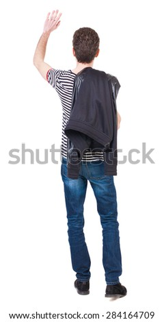 Back view of beautiful man welcomes. man hand waving from. Rear view  people collection.   Isolated over white background. Putting the jacket on the guy waving his right shoulder with his other hand. - stock photo