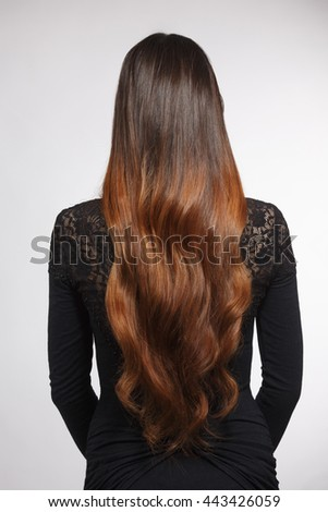 Back view of beautiful woman demonstrating her gorgeous brown hair. Pretty lady with modern hairstyle in studio. - stock photo