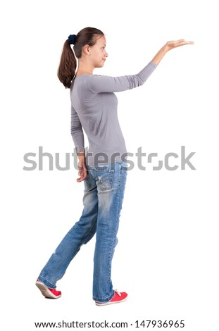 Back view of Beautiful woman in  jeans looking at wall and Holds a hand up. Rear view people collection.  backside view of person.  Isolated over white background.