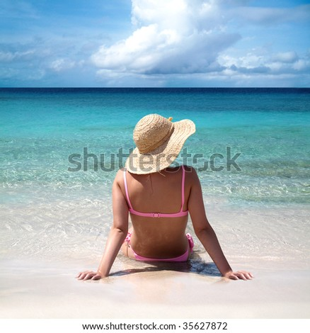 Back view of beautiful woman sitting on seashore and sunbathing
