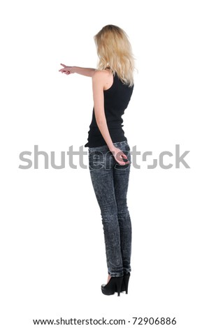 Back view of beautiful young blonde woman pointing at wall. Rear view people series. Isolated over white background. - stock photo