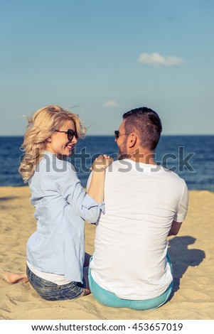Back view of beautiful young couple in casual clothes and sun glasses looking at each other and smiling while sitting together on sunny beach - stock photo