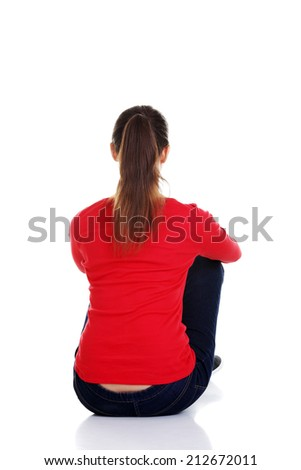 Back view of beautiful young woman sitting on the floor and looks into the distance. Isolated over white background.