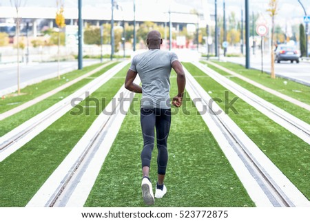 Back view of black man running in urban background. Male doing workout outdoors.