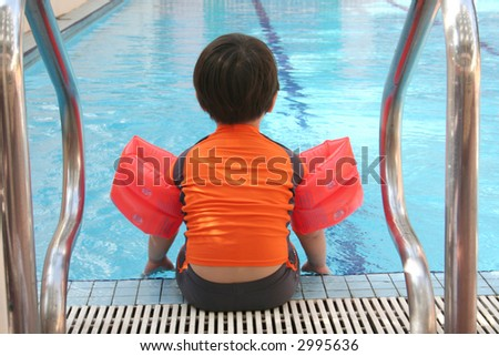 Back view of boy with swimsuit sitting at the swimming pool - stock photo