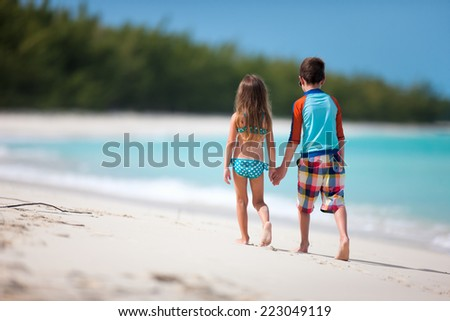 Back view of brother and sister walking at tropical beach - stock photo