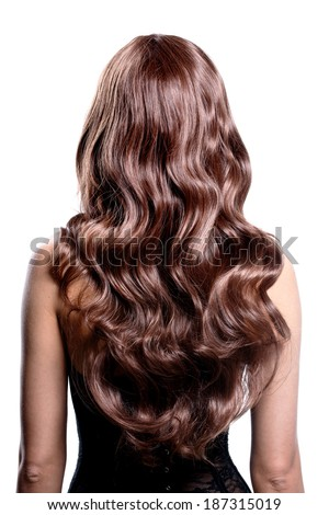Back view of brunette woman with long black curly hair posing at studio. - stock photo