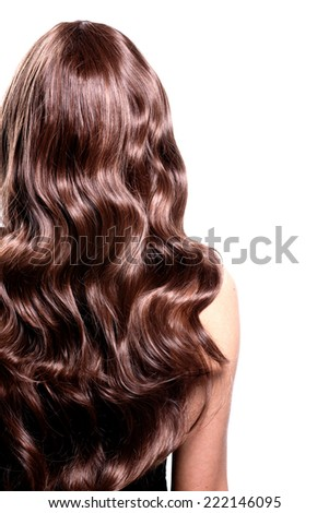 Back view of brunette woman with long black curly hair posing at studio.