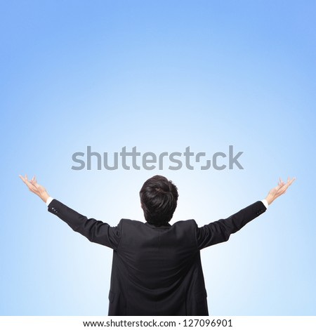 back view of business man arms up and looking to empty copy space isolated on blue sky background, asian model - stock photo