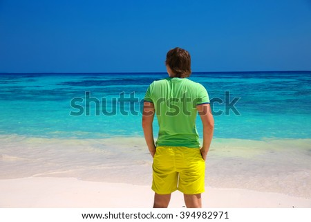 back view of business man enjoying good life on exotic beach, guy looking on seaside, tropical island background. Travel concept. - stock photo