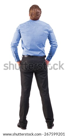 back view of Business man  looks ahead. Young guy in pink shirt watching.  Rear view people collection. broad-office worker with his hands in his pockets looking to the sky - stock photo