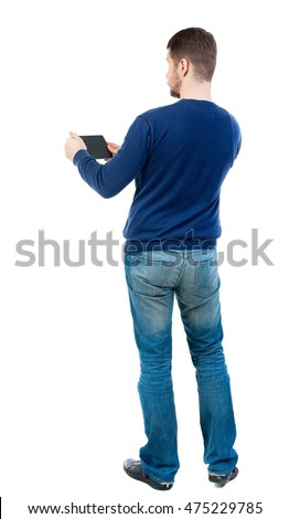 back view of business man uses mobile phone. backside view of person. bearded man in blue pullover is played on a tablet.