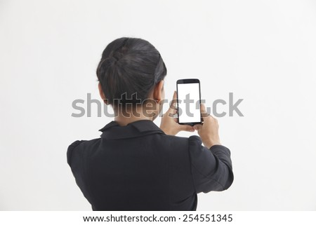 Back view of business woman self portrait with smart phone - stock photo