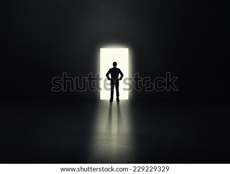 back view of businessman before the open door in a dark room - stock photo