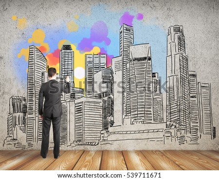Back view of businessman drawing creative city sketch on concrete wall. Architecture concept