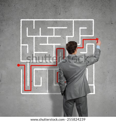 Back view of businessman drawing labyrinth on wall - stock photo