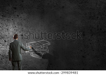 Back view of businessman drawing money banknotes on wall - stock photo