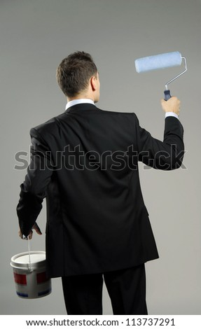 Back view of businessman holding can of paint and brush. - stock photo