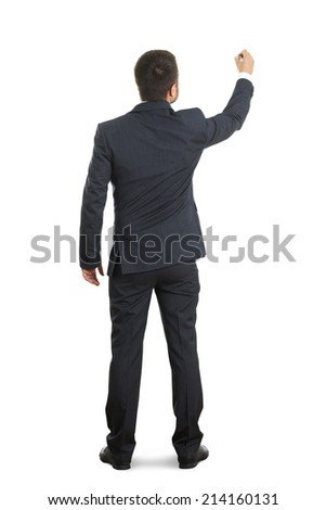back view of businessman in formal wear writing on white wall - stock photo