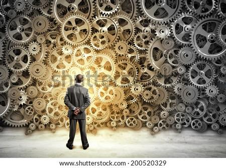 Back view of businessman looking at mechanism of cogwheels - stock photo