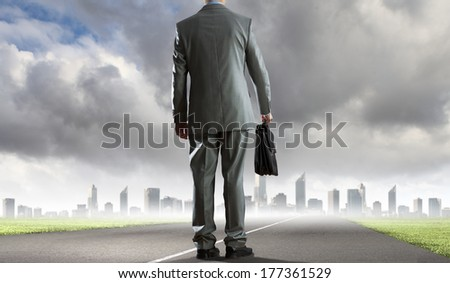 Back view of businessman on road with suitcase in hand
