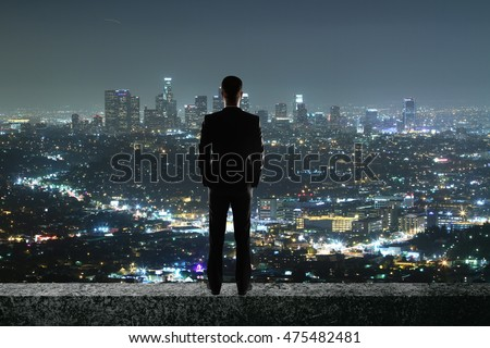 Back view of businessman on rooftop looking at illuminated night city. Research concept