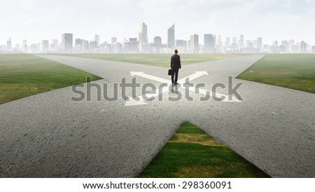 Back view of businessman standing at crossroads and making choice - stock photo