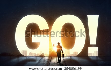 Back view of businessman standing in light of GO word - stock photo
