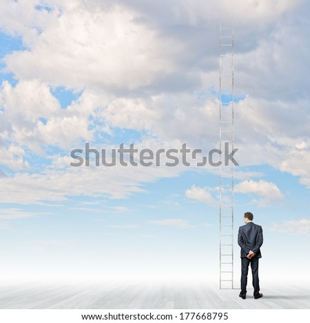 Back view of businessman standing near long ladder to sky - stock photo