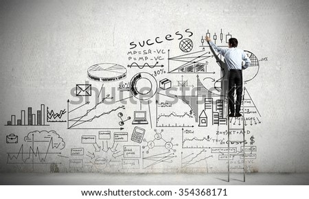 Back view of businessman standing on ladder and drawing sketches on wall - stock photo