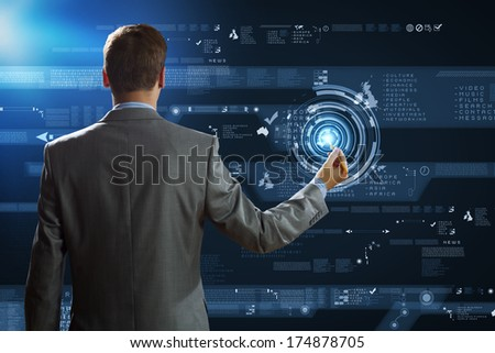 Back view of businessman touching icon of media screen - stock photo
